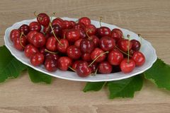 Ripe red cherries on a white plate on a wooden table. Around the green leaves. Royalty Free Stock Photography