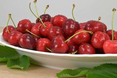 Ripe red cherries on a white plate on a wooden table. Around the green leaves. Stock Photography