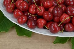 Ripe red cherries on a white plate on a wooden table. Around the green leaves. Stock Image