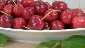 Ripe red cherries on a white plate on a wooden table, Around the green leaves. Slider shot stock footage