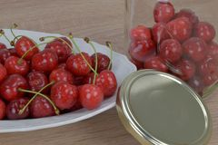 Ripe red cherries on a white plate on a wooden table. Homemade cherry jar. Royalty Free Stock Photos