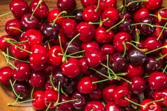 Ripe red cherries in wooden bowl stock images