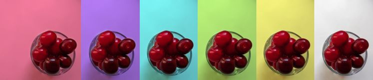 Ripe red cherry berries-fruits inside the glassful - top view, multicolored set. Juicy stone fruit cherry in a round glass container, isolated, close-up on a stock photo
