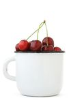 Ripe red cherry in an enamel cup. On a white background Stock Photos