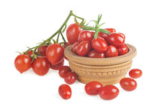 Ripe red cherry tomatoes branch in a wooden plate on a white background. stock photo