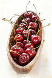 Ripe red cherry with water drops in a wooden elongated plate on an old painted table close up Royalty Free Stock Photography