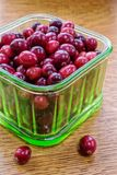 Ripe red cranberries in green glass container Royalty Free Stock Photos