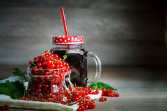 Ripe red currant and black currant juice on a wooden table. Stock Images