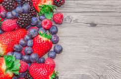 Ripe red fruits on wooden table Royalty Free Stock Photos