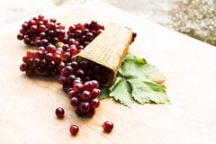 Ripe red grape with leaves  in basket on a wooden table. Royalty Free Stock Images