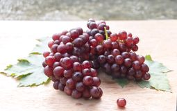 Ripe red grape with leaves  on a wooden table background.  Royalty Free Stock Photography