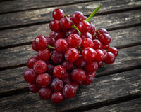 Ripe red grape. Pink bunch in a old rustic wooden table Royalty Free Stock Photos
