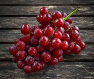 Ripe red grape. Pink bunch in a old rustic wooden table Stock Photo