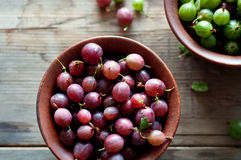 Ripe red and green gooseberry in bowls Stock Photo