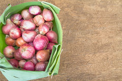 Ripe red onions in banana leaf on vintage grunge wooden background Royalty Free Stock Photo