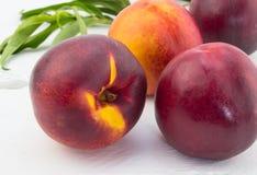 Ripe red and orange nectarines on white wood background Stock Photos