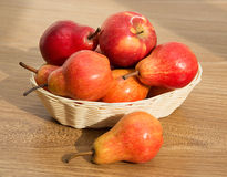 Ripe red pears and apple in the rod basket on the wooden table Royalty Free Stock Photos
