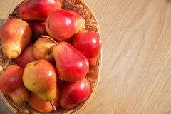 Ripe red pears in the rod basket on the wooden table Royalty Free Stock Images