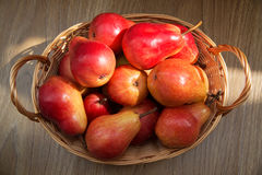 Ripe red pears in the rod basket on the wooden table Royalty Free Stock Photo