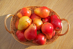 Ripe red pears in the rod basket on the wooden table Stock Photography