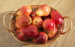 Ripe red pears in the rod basket on the wooden table Royalty Free Stock Photography