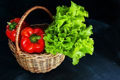 Ripe red peppers and bunch of green salad in wicker basket on dark background. stock photo