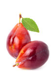 Ripe red plum with leaf. Isolated on white background Royalty Free Stock Images