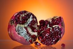Ripe red pomegranate, break in half, juicy corn Royalty Free Stock Image