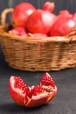 Ripe red pomegranates in wicker basket and seeds in spoon closeup photography on black background. stock photo