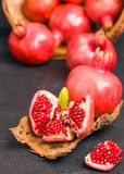 Ripe red pomegranates in wicker basket and seeds in spoon closeup photography on black background. royalty free stock photo