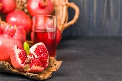 Ripe red pomegranates in wicker basket and seeds in spoon closeup photography on black background. stock image
