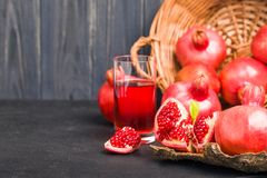 Ripe red pomegranates in wicker basket and seeds in spoon closeup photography on black background. stock photos