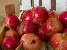 Ripe red pomegranates in a wooden box on brown burlap Stock Photography