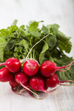 Ripe red radish with leaves on a wooden table close-up. Fresh ve. Getables. Healthy eating Royalty Free Stock Photos