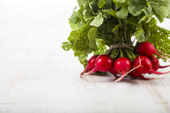 Ripe red radish with leaves on a wooden table close-up. Fresh ve. Getables. Healthy eating Royalty Free Stock Image