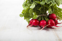 Ripe red radish with leaves on a wooden table close-up. Fresh ve. Getables. Healthy eating Royalty Free Stock Photography
