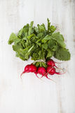Ripe red radish with leaves on a wooden table close-up. Fresh ve. Getables. Healthy eating Stock Photo