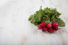 Ripe red radish with leaves on a wooden table close-up. Fresh ve. Getables. Healthy eating Royalty Free Stock Photo