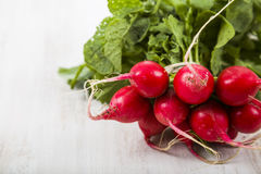Ripe red radish with leaves on a wooden table close-up. Fresh ve. Getables. Healthy eating Stock Image