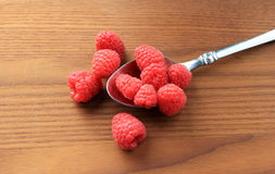 Ripe red raspberries spilling over from silver spoon Stock Photography