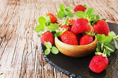 Ripe red raspberries and strawberries in wooden bowl, selective focus. Ripe red raspberries and strawberries in a wooden bowl on the table, selective focus Royalty Free Stock Photos