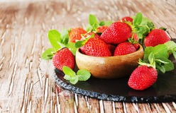 Ripe red raspberries and strawberries in wooden bowl, selective focus. Ripe red raspberries and strawberries in a wooden bowl on the table, selective focus Stock Image