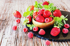 Ripe red raspberries and strawberries in wooden bowl, selective focus. Ripe red raspberries and strawberries in a wooden bowl on the table, selective focus Royalty Free Stock Photo