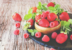 Ripe red raspberries and strawberries in wooden bowl, selective focus. Ripe red raspberries and strawberries in a wooden bowl on the table, selective focus Stock Images