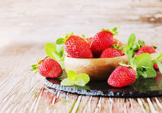 Ripe red raspberries and strawberries in wooden bowl, selective focus. Ripe red raspberries and strawberries in a wooden bowl on the table, selective focus Royalty Free Stock Photography