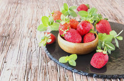 Ripe red raspberries and strawberries in wooden bowl, selective focus. Ripe red raspberries and strawberries in a wooden bowl on the table, selective focus Stock Photo