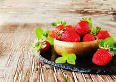Ripe red raspberries and strawberries in wooden bowl, selective focus. Ripe red raspberries and strawberries in a wooden bowl on the table, selective focus Stock Photos