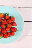 Ripe red strawberries on a blue ceramic plate Royalty Free Stock Images