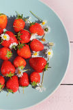 Ripe red strawberries on a blue ceramic plate Stock Images
