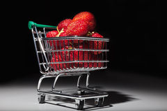 Ripe red strawberries in miniature supermarket trolley Royalty Free Stock Photo